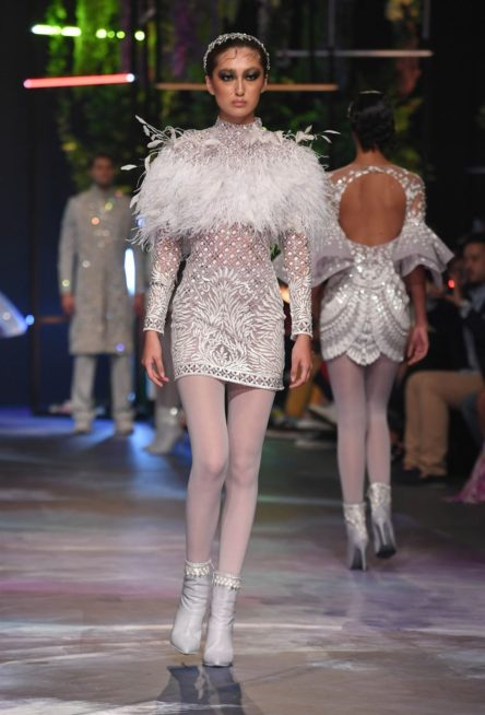 فستان قصير مصمم من القماش الشفاف المزين بالنقشات والزخرفات البيضاء يجمّله الريش عند الصدر والساعدين، نس بطريقة مبتكرة مع الجوارب البيضاء.