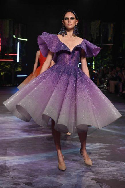 فستان ميدي بتدرجات اللون البنفسجي البراق ذات القصة الكلوش الواسعة مع الاكمام البارزة على شكل كشاكش عريضة.
