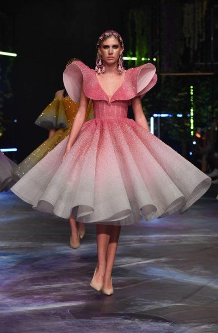 فستان ميدي بقصة الكلوش الواسعة مع الكسرات العريضة يتميز بتناغم لونيه الزهري والابيض مع الاكمام البارزة والعريضة.