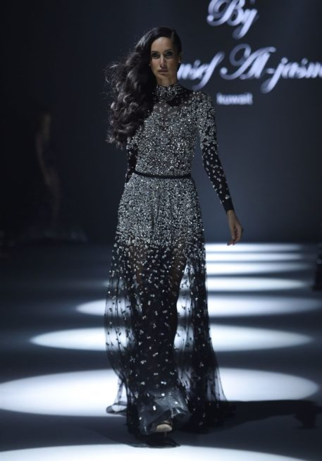 فستان طويل من القماش الشفاف الاسود المزين بالستراس الفضي عند الصدر والخصر، تجمّله الياقة العالية والحزام الاسود الرفيع.