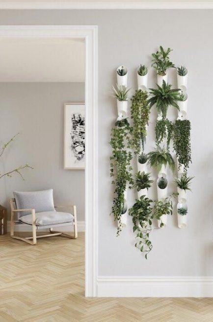 ثبّتي مجموعة من الأواني البلاستيكية ذات التصميم الملفت والموحّد بطريقة متناسقة على الجدار، ووزّعي داخلها النباتات المتنوعة.