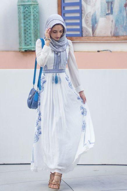 فستان أبيض طويل بقصة الكلوش الناعمة المنسد بسلاسة مع الجسم تزينه التطريزات الزرقاء على شكل أزهار ونسق معه الحجاب الازرق.