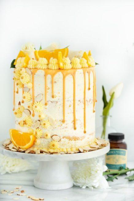 فكرة مميزة لتزيين كيك البرتقال مع اعتماد الكريما البيضاء والبرتقالية واختيار شرائح البرتقال الصغيرة الى جانب أشكال الازهار الصغيرة.