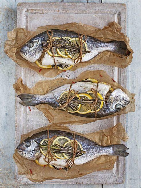 وزّعي قطع السمك المشوية على طبق مسطح بشكل عكسي، وزيني كلاً منها بشرائح الليون واكليل الجبل ولفيها بحبال صغيرة لزينة ناعمة.