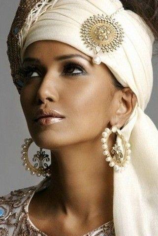 لفة الحجاب المستوحاة من الحضارة الصحراوية العربية تضفي التميز والفرادة الى الاطلالة، مع هذه اللفة الجانبية بالحجاب الابيض والذهبي مع الأكسسوار بشكل الشمس.