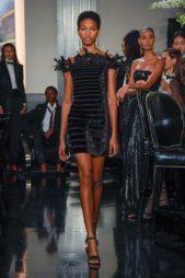 فستان لافت بتدرجات اللون الاسود بقصته المتناغمة مع الجسم والاكتاف المكشوفة والريش الاسود الذي يزين الاكتاف والصدر.