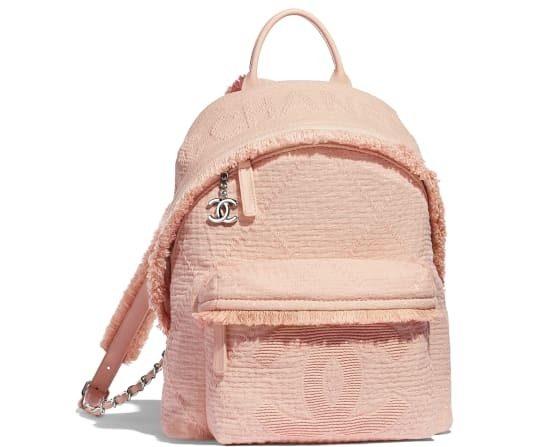 حقيبة ظهر زهرية اللون من شانيل تتميز بحجمها المتوسط مع الجيبة الامامية البارزة المزينة بشعار الدار واسم العلامة التجارية مع الشراشيب الصغيرة.