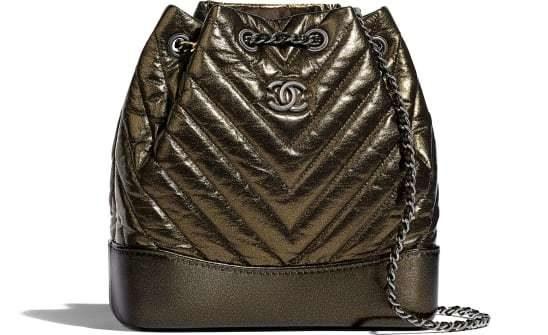 ما رأيك بهذه الحقيبة للظهر باللون البرونزي البراق ذات القاعدة البنية المصنوعة من الجلد مع الحزام الفضي الرفيع يزينها شعار الدار الفضي ايضاً؟