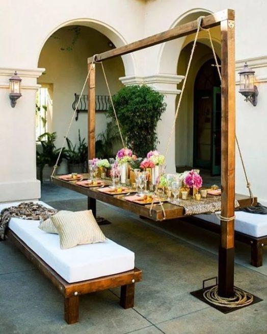 في حديقتك أيضاً يمكنك اللجوء إلى صيحة الطاولة المعلقة والتي نراها في هذه الصورة مربوطة بحبال تلتف حول إطار خشبي عالٍ.