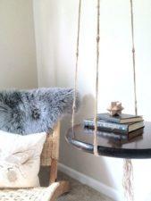 طاولة دائرية جانبية مصنوعة من الخشب المطلي باللون الأسود، تم تعليقها بالسقف من خلال تركيزها بشكل متوازن بين الحبال.
