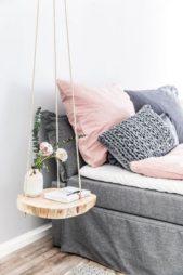 طاولة جانبية صغيرة، استخدمت الحبال لتعليقها في السقف وهي عبارة عن قطعة خشب من جزع شجرة كبير.