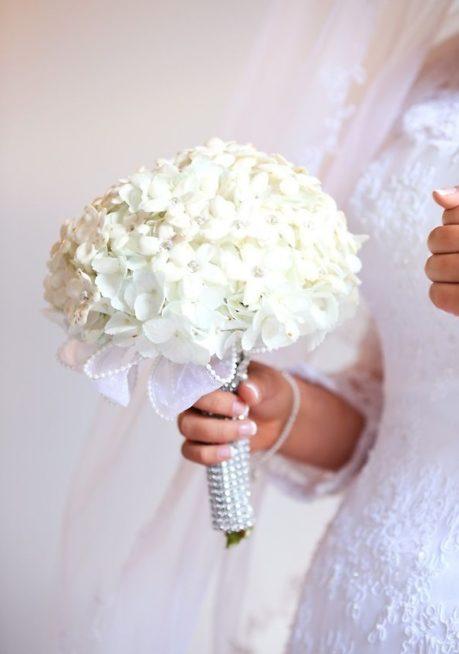 باقة عروس كروية مكونة من الياسمين المرصع بستراس فضي لامع، يلتف حول عنق الباقة شريط أبيض ويحيط بمسكتها قطعة مصنوعة من الحبيبات الفضية.