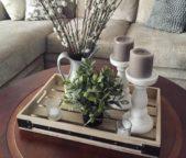 إختاري صينية خشبية كبيرة ذات تصميم ناعم ثبتي عليها قاعدتين متشابهتين للشموع مع أواني ملفتة ومزينة بالنباتات الخضراء.