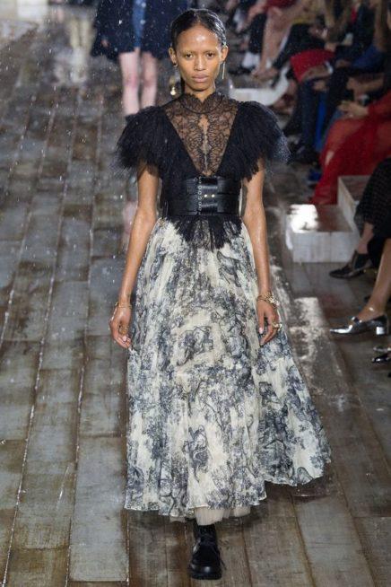 <p><strong>Christian Dior - كريستيان ديور</strong></p> <p>تنورة ناعمة طويلة باللونين الابيض والاسود منسق باسلوب ملفت مع البلوزة السوداء ومزنية عند الخصر بحزام اسود عريض.</p>