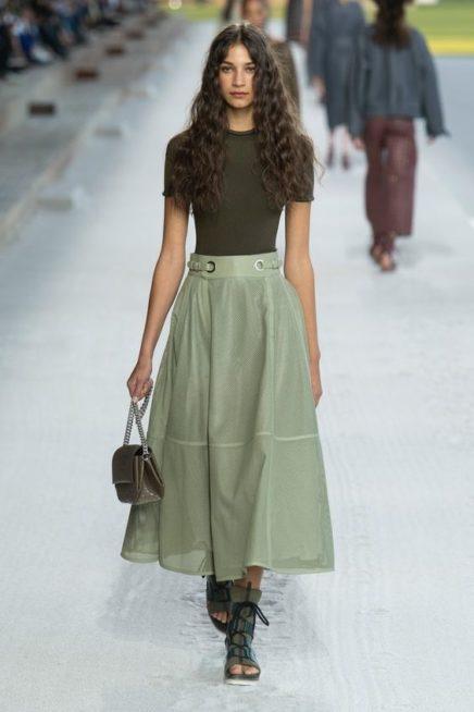 <p><strong>Hermès - هرميس</strong></p> <p>قدّمت هذه الدار اطلالة ملفتة مع التنورة الطويلة الخضراء بقصة الكلوش الناعمة ونسقتها مع البلوزة الزيتية.</p>