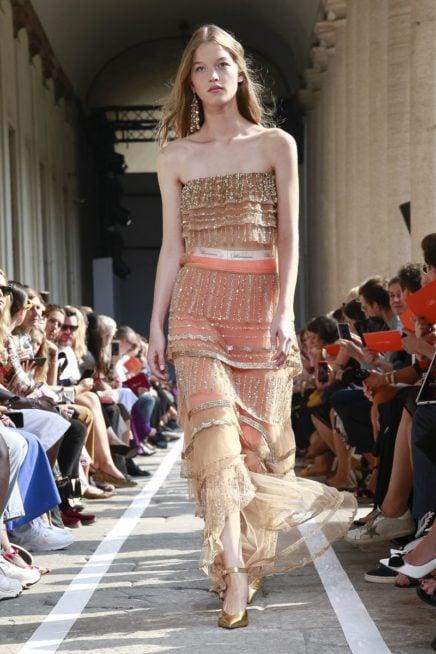 <p><strong>Blumarine - بلومارين</strong></p> <p>لسهرات الشتاء اختاري هذا الفستان باللون المشمشي المزين بشراشيب بالولن الذهبي، مع تنورته المصممة في الاسفل من القماش البيج الشفاف.</p>