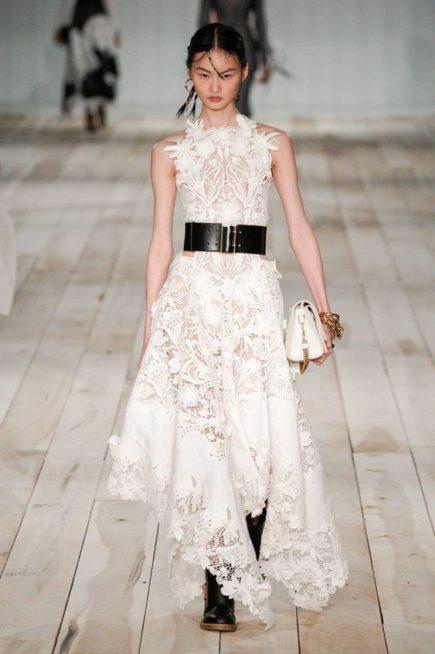 <p><strong>Alexander McQueen - الكسندر ماكوين </strong></p> <p>فستان طويل متفاوت الطول عند الاسفل بقصة كلوش ناعمة صمم من الدانتيل المخرّم على شكل أزهار ويزيّنه الحزام الاسود العريض عند الخصر.</p>