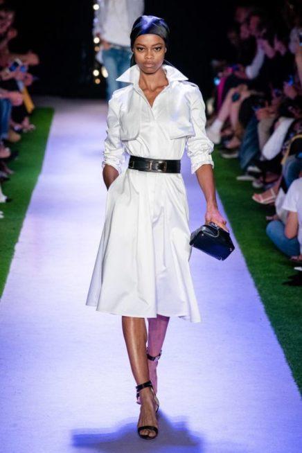 <p><strong>Brandon Maxwell - براندون ماكسويل </strong></p> <p>فستان ابيض ميدي مصمم من القماش اللماع مع الياقة العالية على شكل قميص، يزيّنه الحزام الاسود الجلدي العريض عند الخصر.</p>
