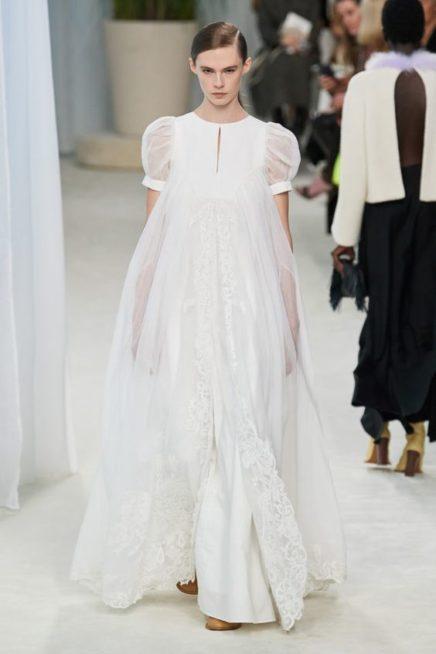 <p><strong>Loewe - لويفي</strong></p> <p>فستان ابيض طويل بقصة واسعة منسدلة بسلاسة مع الجسم يتميّز بقماشه الشفاف المزين عند الاطراف بالدانتيل الناعم مع الاكمام الواسعة.</p>