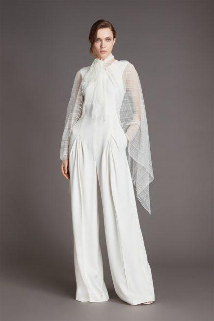 """<div style=""""direction: rtl;"""">إعتمد المصمم رولان موريه الجامبسوت الأبيض في مجموعة فساتين الأعراس لربيع 2021، ويُتيح للعروس إختياره إمّا في يوم الزفاف إذا كنت تحبين هذا الستايل، أو حتى يمكن اعتماده في سهراتك قبل موعد العرس أو للقيام بجلسات التصوير.</div>"""