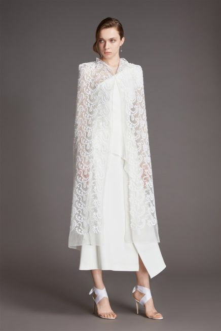"""<div style=""""direction: rtl;"""">مزيج بين الدانتيل وقماش الكريب في فستان الزفاف لربيع 2021 من تصميم رولان موريه، وهنا يظهر الستايل ملكيّاً مع الكاب الخفيف الذي يتم وضعه فوق الفستان الأساسي الأبيض الميدي.</div>"""
