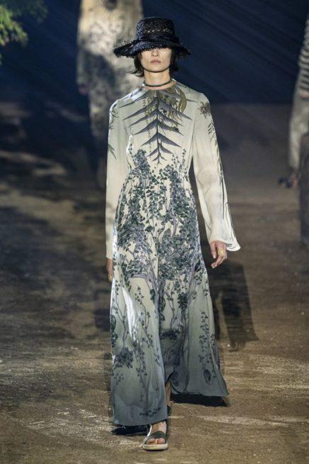 <p><strong>Dior - ديور </strong></p> <p>فستان طويل بقصة متناسقة مع الجسم منسدلة بسلاسة يتميز بلونه الاوف وايت الذي تزينه نقشات النباتات المتداخلة.</p>