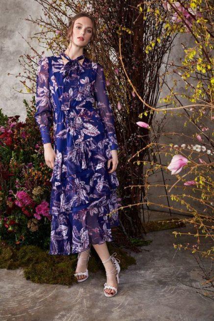 <p><strong>Marchesa - ماركيزا </strong></p> <p>فستان طويل أزرق اللون متعدد الطبقات بقصة متناسقة ومستقيمة مع الجسم تزيّنه أوراق الأشجار الكبيرة باللون الابيض مع الاكمام الشفافة والعقدة الناعمة عند العنق.</p>