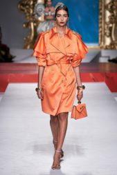 <p><strong>Moschino - موسكينو</strong></p> <p>اطلالة مميزة باللون البرتقالي مع الفستان المصمم من القماش اللماع ذات الأكمام القصيرة المتعددة الطبقات والياقة العريضة يجمّله الحزام القماشي من اللون عينه.</p>