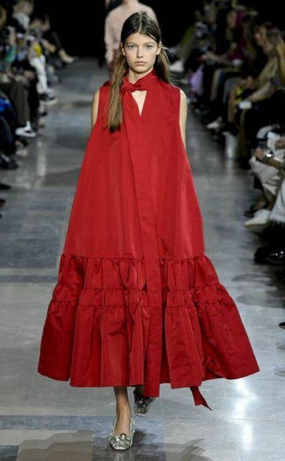 <p><strong>Rochas - روشا</strong></p> <p>فستان أحمر أحادي اللون مصمّم بقصة كلوش واسعة وفضفاضة مع الكشاكش العريضة التي تزيّنه عند الأسفل، وتجمّله العقدة عند العنق المنسدلة على طول الفستان.</p>