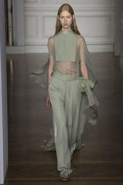 <p><strong>Valentino - فالنتينو </strong></p> <p>سروال بالازو ذات لون اخضر باستايل مزيّن عند الجانبين بتقليمات بيضاء عريضة ونسقت معه البلوزة الشفافة ذات الياقة العالية.</p>