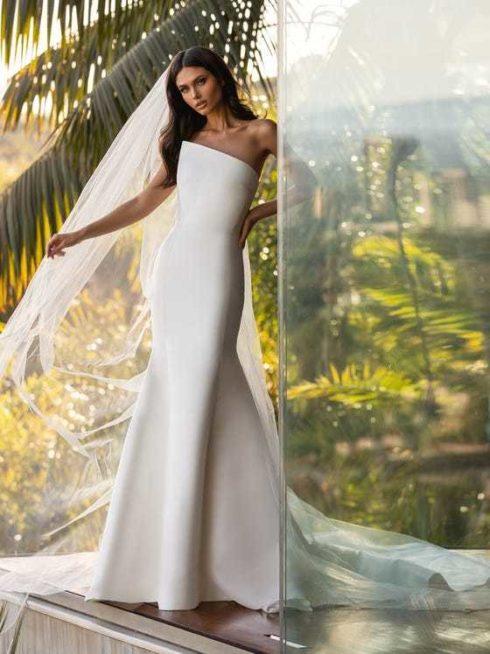 """<p style=""""text-align: right;"""" dir=""""RTL"""">من خامة الكريب التي لا يضاهى جمالها، صنع هذا الفستان السترابلس بقصته المائلة والمميزة عند الصدر. وتظهر في القسم السفلي قصة ذيل الحورية التي جعلت التصميم يضج أنوثة وسحراً. موديل بسيط خالي من التفاصيل والزخرفات إلا أنه أكثر من رائع.</p>"""