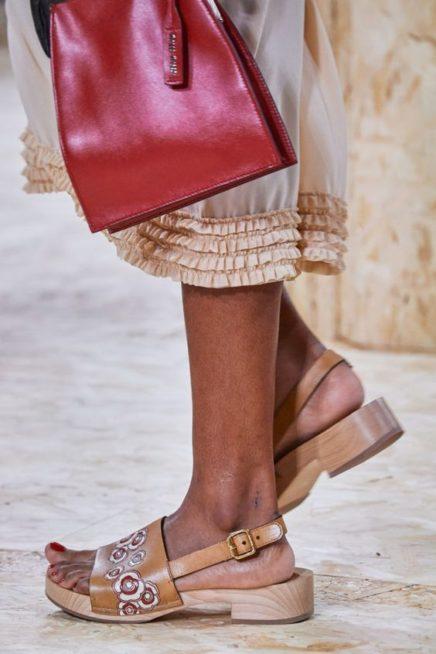 <p><strong>Miu Miu - ميو ميو </strong></p> <p>حذاء خشبي ذات كعب منخفض يتميّز بلونه البيج الفاتح المزين عند الجهة الامامية بنقشات الأزهار الملونة المتفاونة الأحجام مع الحزام الرفيع عند اسفل القدم.</p>