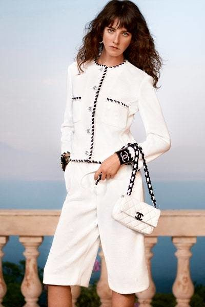بدلة نسائية أنيقة باللون الأبيض مع الشورت البرمودا الواسع المنسق مع الجاكيت البيضاء المزيّنة عند الأطراف باللون الأسود.