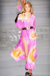 <strong>Blumarine - بلومارين</strong><br /><br />فستان طويل مصبوغ بألوان صيفية حيوية تمتزج ببعضها البعض حيث حيث يتداخل اللون البنفسجي مع الاصفر والابيض، ويتميّز تصميمه بالشقين الجانبيين.