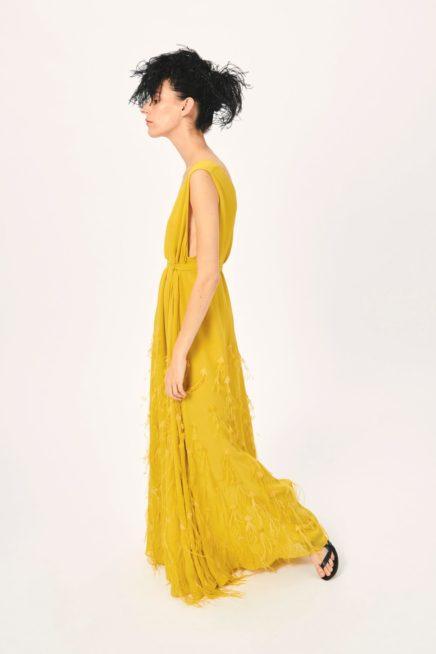 شاهدي في هذه الصور تصميم فستان طويل بقصة مستقيمة ومنسدلة بسلاسة مع الجسم، يتميز بلونه الأصفر المائل إلى الخردلي، مع التطريزات الناعمة ولمسات الريش المنسدل منه.