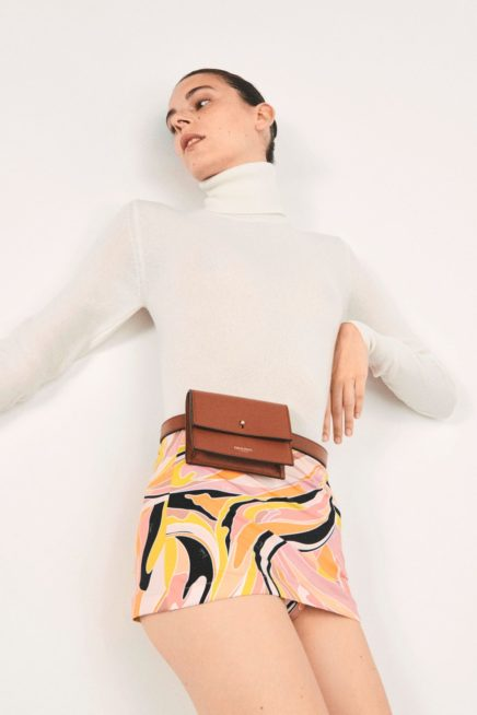 إطلالة ريترو أنيقة بلمسة كلاسيكية حيوية مع التنورة القصيرة الضيقة المميزة بنقشات الابيض والاسود والاصفر. ونسقت مع البلوزة ذات الياقة العالية باللون الأبيض.