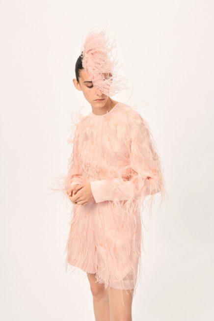 عبّري عن أنوثتكِ مع هذا الفستان القصير باللون الزهري الفاتح وذات القصة المستقيمة، حيث زين بالريش الناعم الزهري اللون، ومعه القبعة الصغيرة من الريش أيضاً.