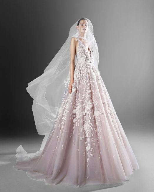 فستان زفاف مميز بقصته الملكية ولونه الزهري الباستيل. تزيّنه تطريزات الأزهار البيضاء التي تغطيه عند الصدر والخصر نزولاً الى وسط القسم السفلي، وتجمّله الفتحة على الصدر. الواسعة