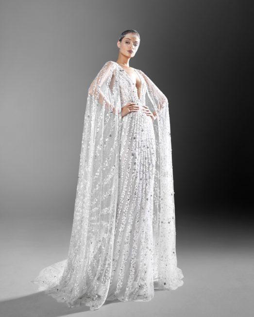 ستايل الكاب رائج  جداً في عالم الموضة لعام 2021، وقد أضافه زهير مراد الى هذا الفستان الضيق مع الفتحة الواسعة على الصدر. وقد رصّع الكاب كما الفستان بالتطريزات البرّاقة المستوحاة من حقول الازهار.