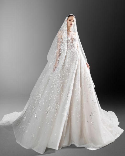 لعروس تغرق بعالم الازهار والورود، اليك هذا الفستان الأبيض الفاخر المصمم بقصة ملكية ناعمة مع التطريزات على شكل أزهار فضية وبراقة. ونسّقت معه الطرحة الطويلة المزينة ايضاً بتطريزات أزهار فضية.