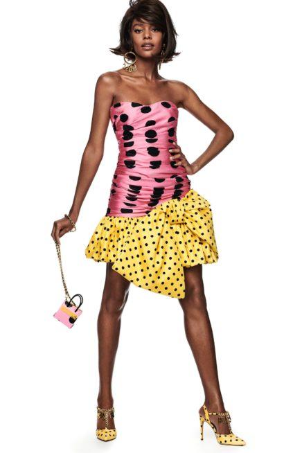 فستان قصير سترابلس باللون الزهري في قسمه العلوي مع ستايل الدرابيه الذي يجعله أنثوياً بامتياز. وقد أضيف اليه في طرفه السفلي فيونكة صفراء مع الكشكش المنقط بالاسود.