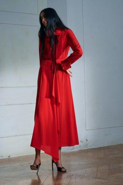 فستان احمر طويل بقصة ناعمة وبسيطة تزينه الكشاكش العريضة عند الاطراف والياقة العريضة بيتر بان مع العقدة السوداء الرفيعة.