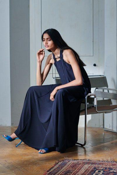لإطلالة اكثر تألقاً وبساطة، صمّم هذا الفستان الطويل الواسع بلونه الكحلي الدافئ، بقصة واسعة مع الشرائط السوداء الرفيعة التي تزينها عند الكتفين.