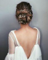 شينيون ناعم وعصري يأخذ شكل رفعة الكعكة المنخفضة. ونرى في الصورة أن الشعر أخذ كله إلى الخلف وقد لف مع أغصان الزهور الصغيرة والناعمة بشكل ناعم وأنيق جداً ما جعل من الموديل تسريحة عرائسية فائقة الجمال والنعومة.