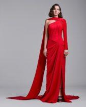 الأحمر الصاخب كسر حدّة اللون الأسود وأضفى الرونق إلى اطلالة المرأة. وقد أتى الفستان بقصة متاغمة مع الجسم، تجمّله القصة الدرابيه مع الشق الجانبي القصير.