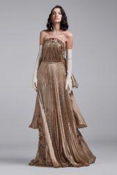 تمايل اللون الذهبي مع الكسرات الصغيرة المتراصة بصيحة الاكورديون أضاف الرقي إلى هذا الفستان السترابلس الذي تجمّله الزخرفات البراقة مع القفازات الطويلة.