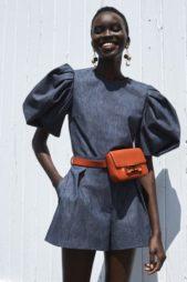 اطلالة كاجوال ناعمة مع الجمبسوت الشورت العملي بقصته المريحة مع الاكمام المنفوشة باللون الكحلي تزيّنه حقيبة الخصر البرتقالية.