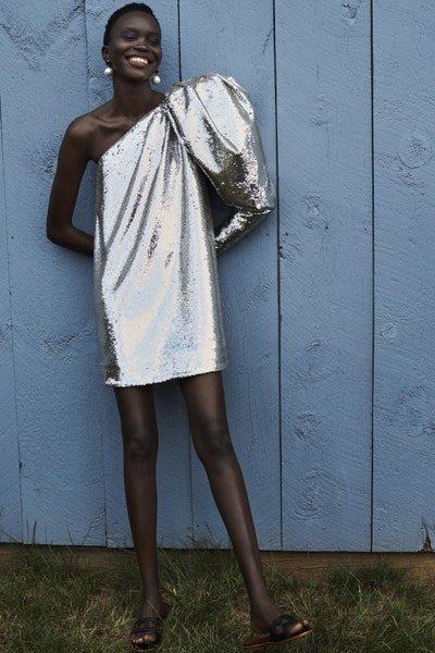 للمرأة الجريئة في إطلالتها في السهرات، فستان قصير باللون الفضي البراق ذات قصة الكتف الواحد مع الكم المنفوش والقصة المستقيمة.
