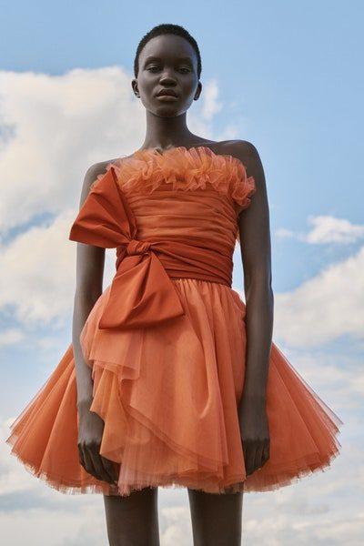 سحر اللون البرتقالي متجلّى بشكل لافت في هذا الفستان القصير المصمم من التول بقصة كلوش ناعمة مع الكشاكش الصغيرة عند الصدر السترابلس، تزيّنه الفيونكة الكبيرة عند الخصر.