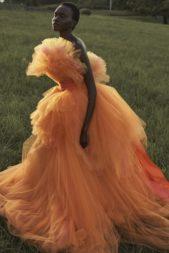 فستان سهرة مصنوع كلّه من قماش التول بطبقات عدّة. يتميّز بلمسات من اللون الزهري تتداخل مع البرتقالي للوك مفعم بالحيوية.